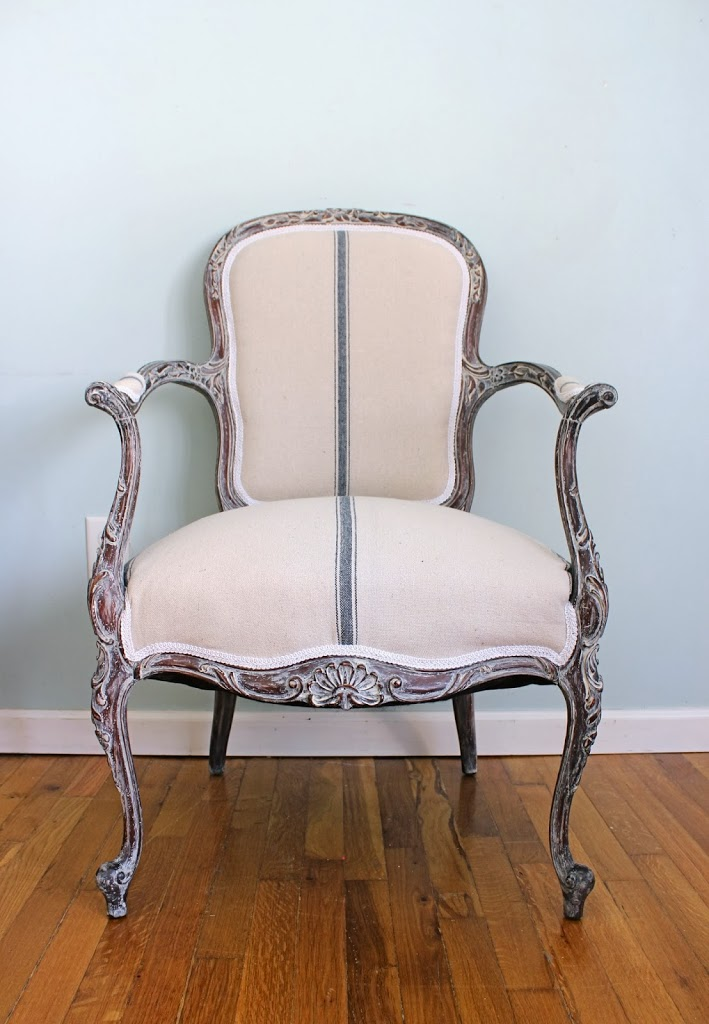 White washed frame of french chair, reupholstered with grain sack fabric and white trim
