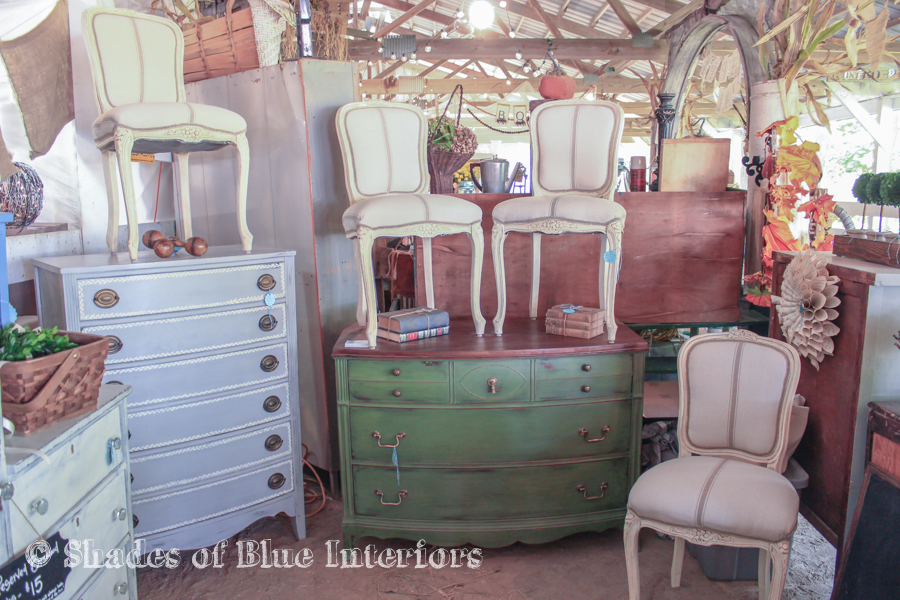 French chairs atop painted dressers in a vintage fair