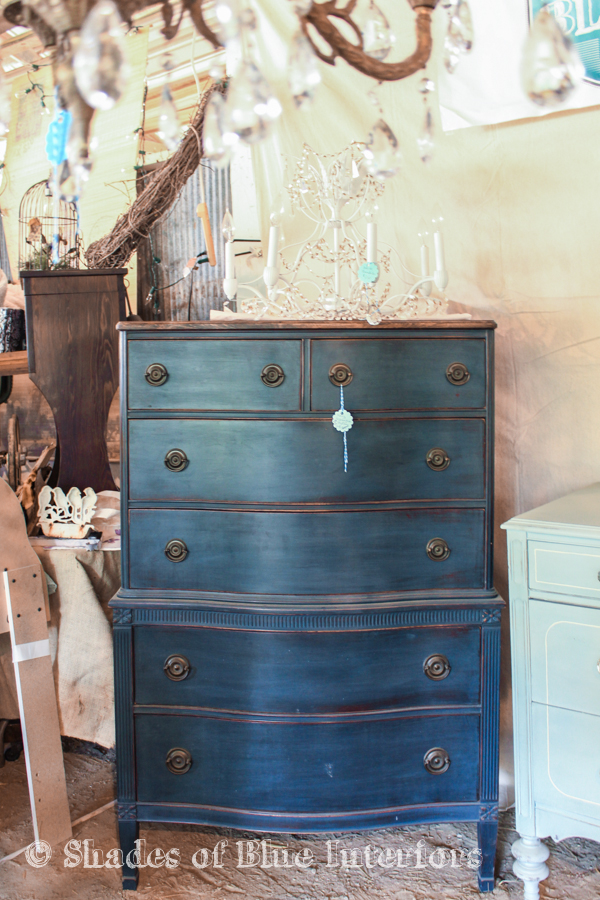 Navy blue dresser with a white chandelier on top - Vintage Market