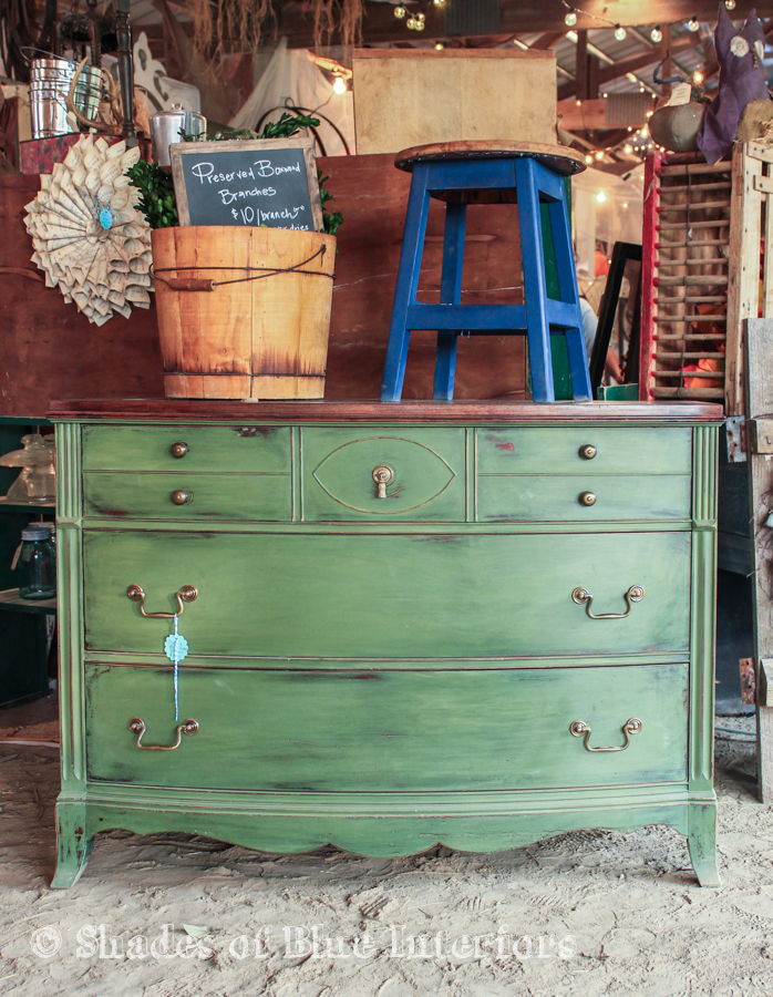 Green dresser with blue stool on top and bucket with preserved boxwood inside.
