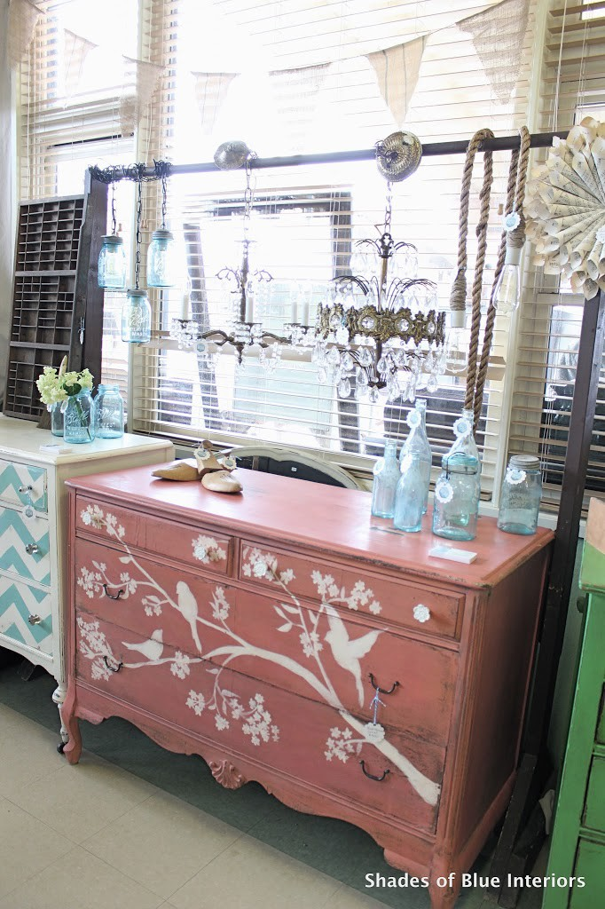 Bird and Branch Coral dresser with blue bottles on top and chandeliers hanging above it.