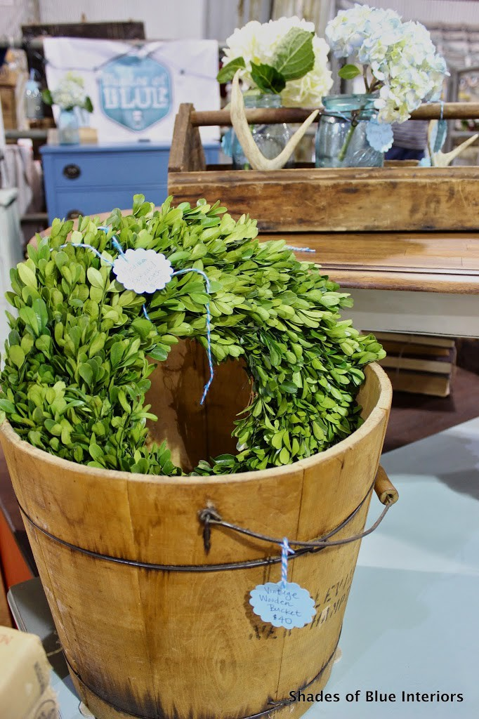 Preserved Boxwood wreath inside a wooden bucket with wooden tray and antlers in the background.