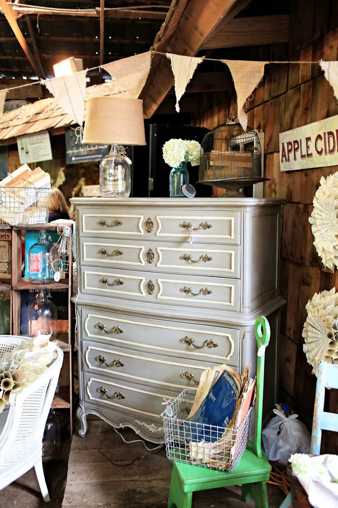 French highboy in gray and white with green stool in front.