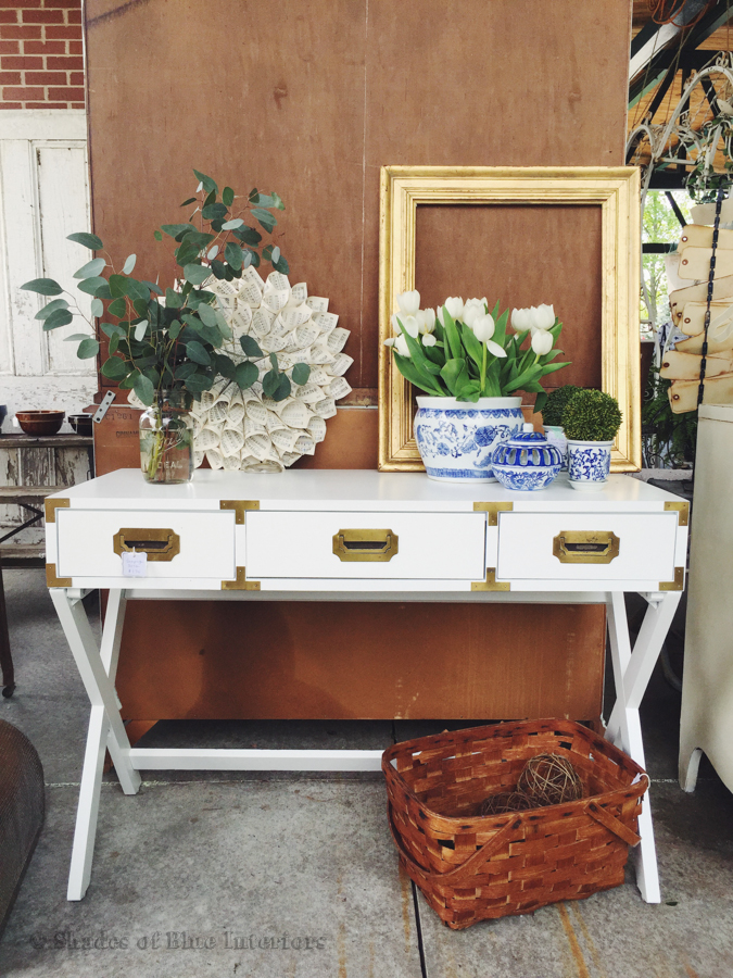 White campaign desk staged with flowers, gold frame, and sheet music wreath.