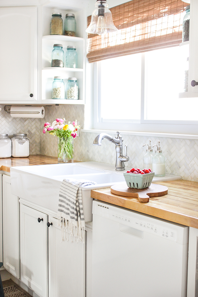 Bamboo shades over farmhouse kitchen sink