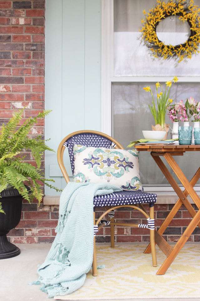 Navy Outdoor Bistro chair with aqua throw and pattern pillow