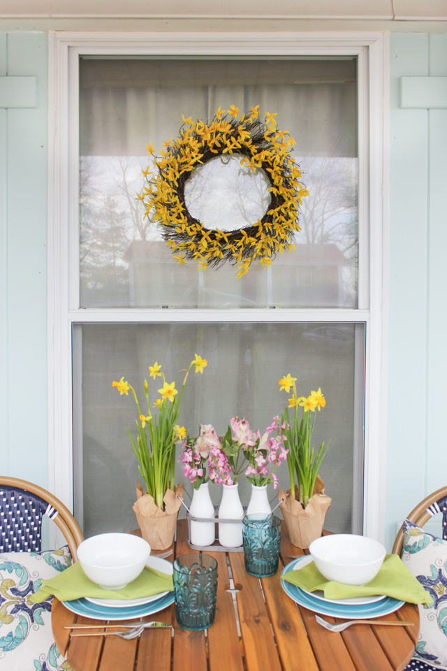 Forsythia wreath hung on outdoor window above table and chairs