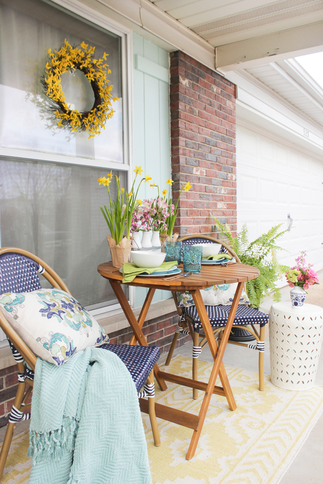 Front Porch Seating area decorated for spring with navy, aqua and pops of yellow