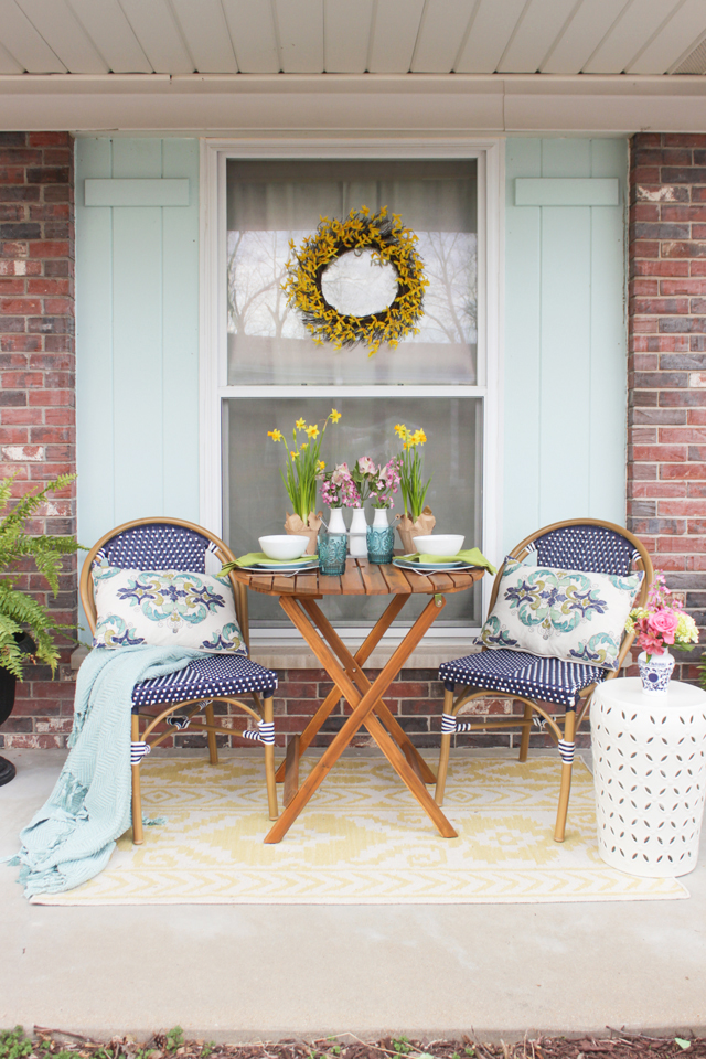 Spring front porch with bistro table and chairs, flowers, and forsythia wreath