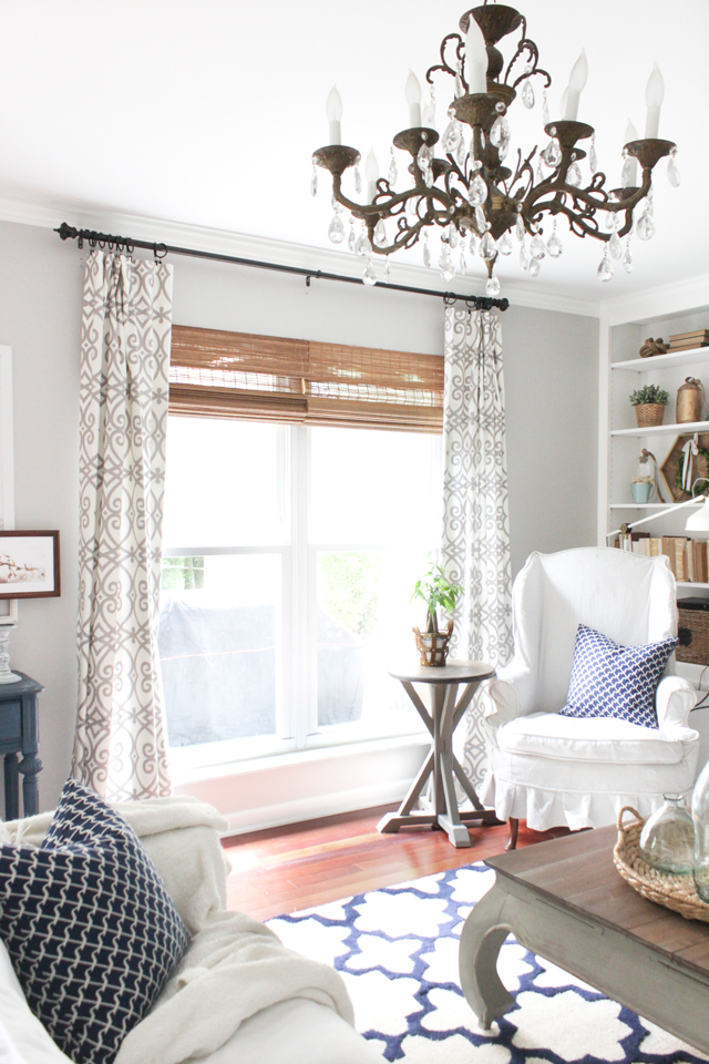 Cozy living room with bamboo shades, patterned curtains, gray walls, and vintage chandelier