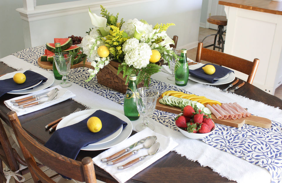 Blue and white runner, navy napkins, white dishes, french flatware, lemons, and fresh flowers