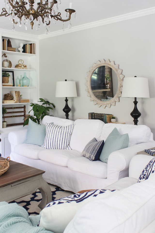 White slipcovered sofas with aqua and navy accents in summer living room