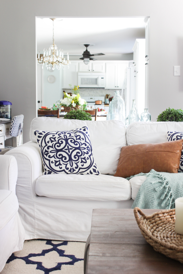 White sofa with navy and white pillow, and camel leather pillow- summer living room