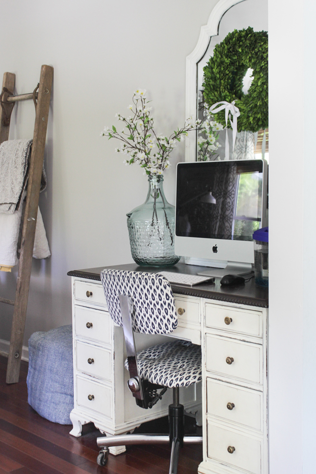 Desk styling with mirror behind the computer and vase with flowers