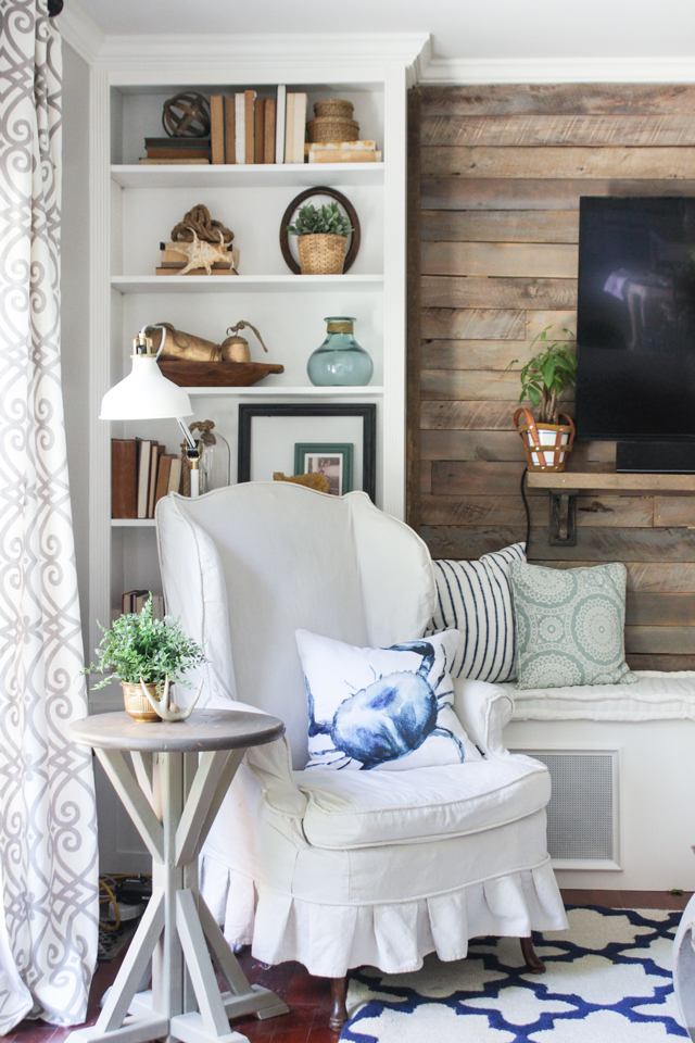Pallet accent wall, built-in bookcase, and slipcovered wing chair