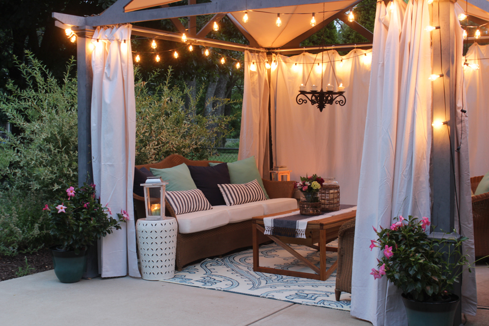 Pergola with edison bulb lights, canvas curtains and cozy seating at dusk