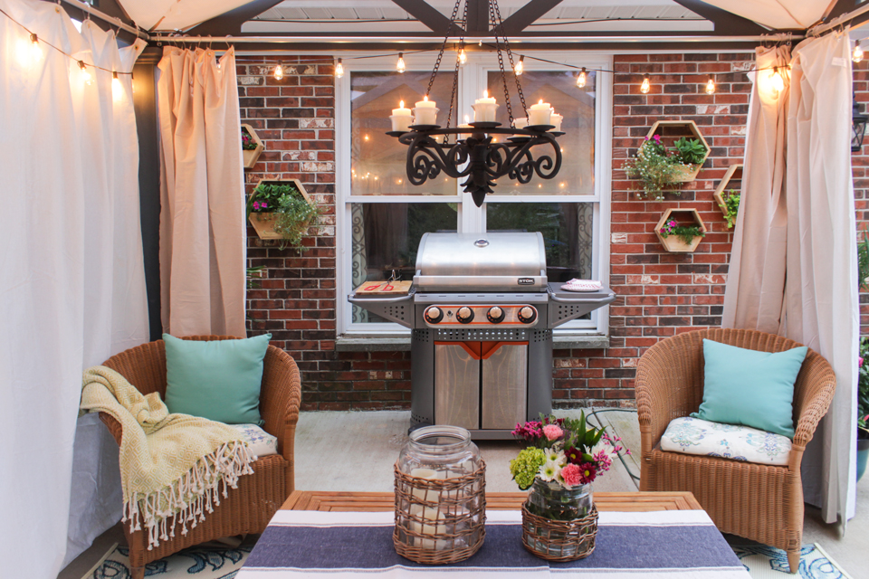 Decorative hex planters on brick, Stok grill, candle chandelier, wicker chairs, canvas curtains
