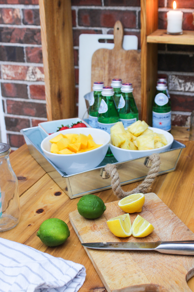 Cut lemons and bowls of fresh fruit for a fruit-kebob station
