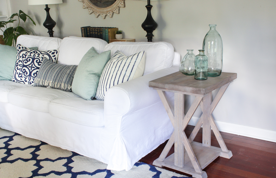 Farmhouse end table with aqua glass bottles on top, white slipcovered sofa, and navy and aqua patterned pillows