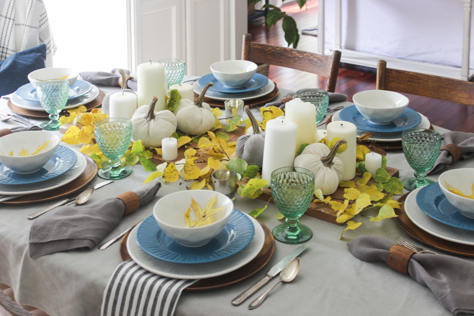 Fall tablescape with white pillar candles, velvet pumpkins, fall foliage, and layered place settings