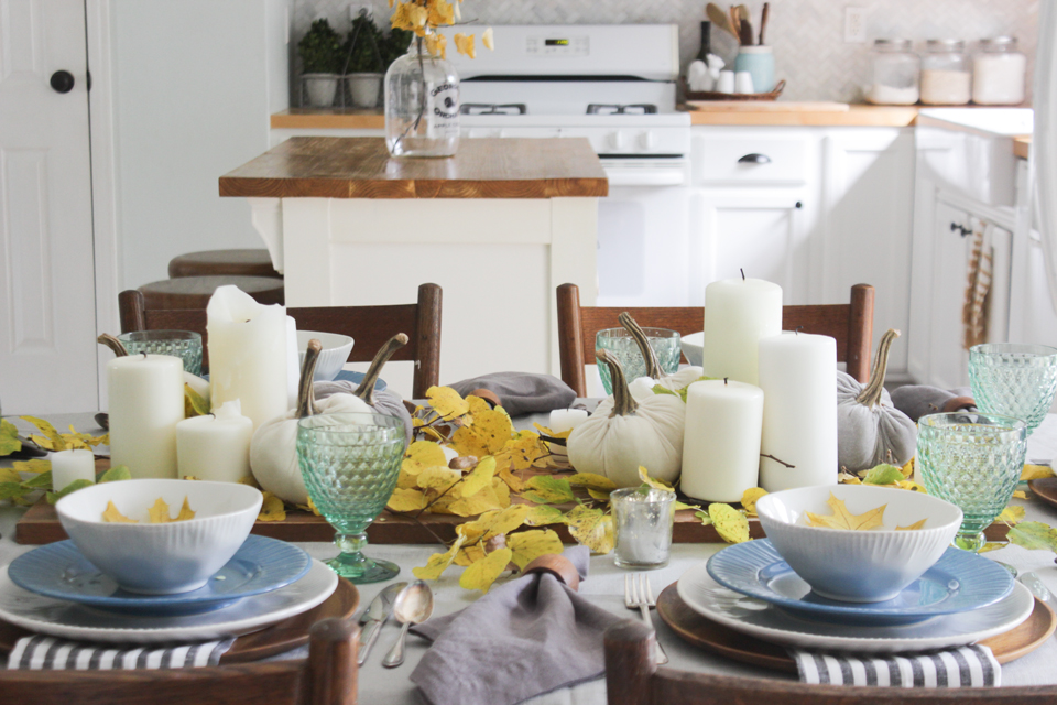 Fall tablescape with pillar candles, velvet pumpkins, and fall foliage