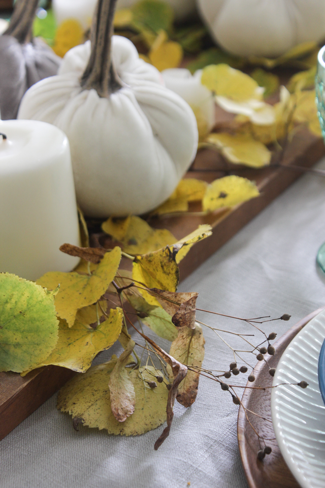 Fall centerpiece with fall leaves, velvet pumpkins, and pillar candles on wooden tray