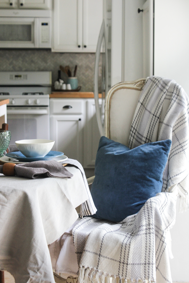 Cozy dining table seat with throw and velvet teal pillow