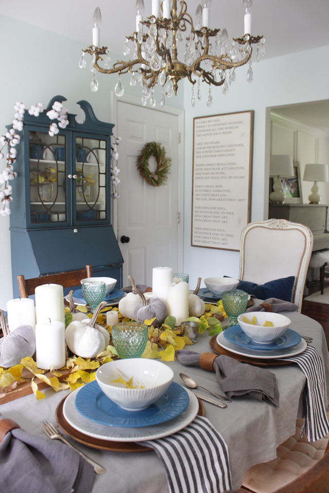 Blue china cabinet, fall tablescape, and brass and crystal chandelier