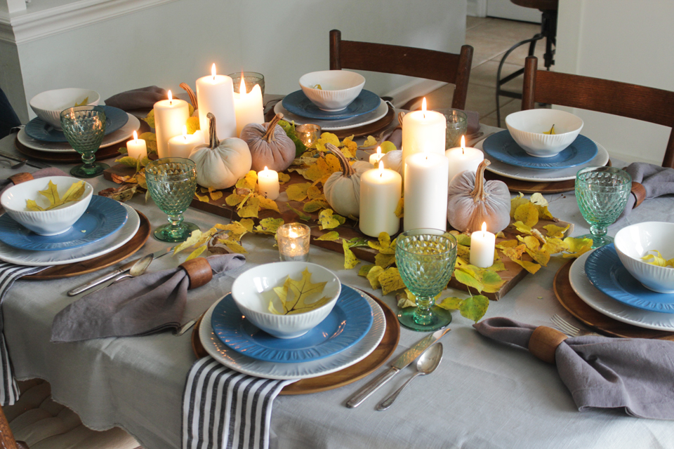 Fall tablescape with pillar candles, pumpkins, fall leaves, and layered place setting