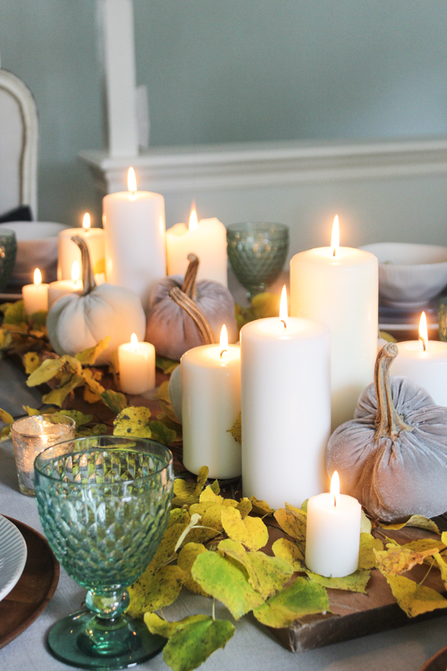 Fall centerpiece with lit pillar candles, velvet pumpkins on a bed of yellow leaves