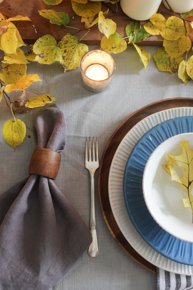 Linen napkin with wooden napkin holder, layered place settings, and fall foliage