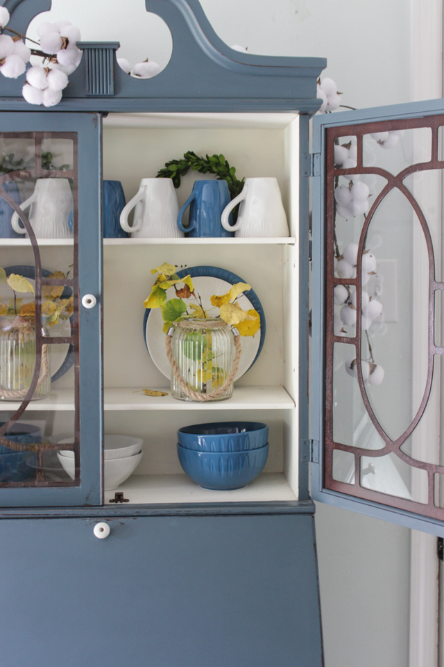 Blue cabinet with blue and white dishes, fall leaves, cotton stems
