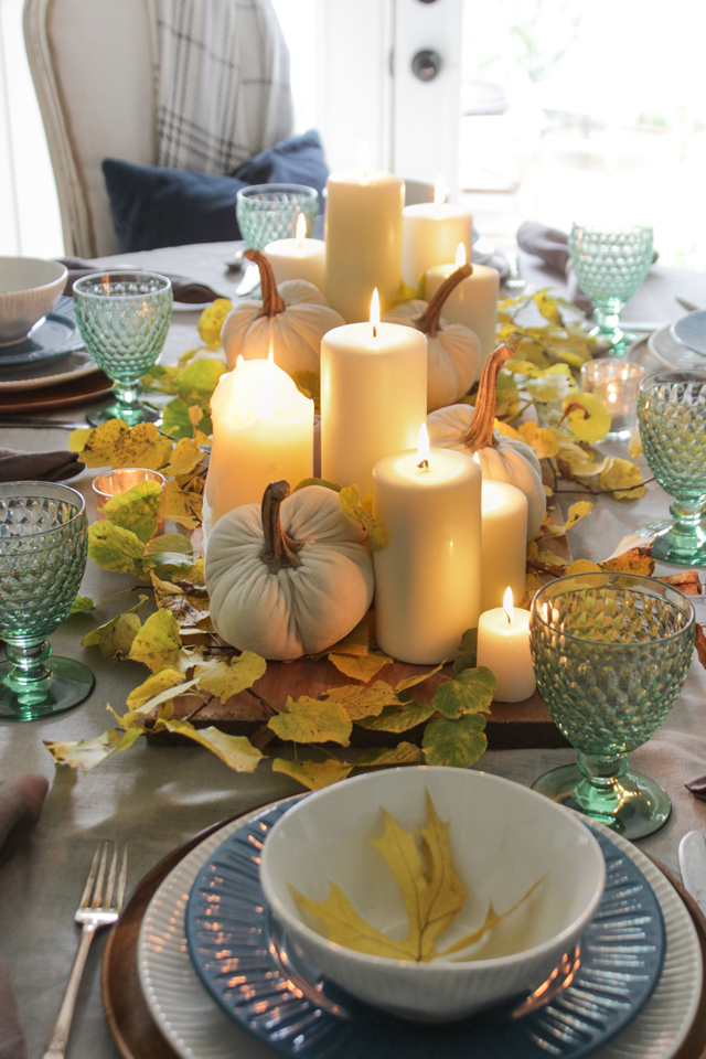 Lit pillar candles in a fall tablescape with fresh cut yellow leaves