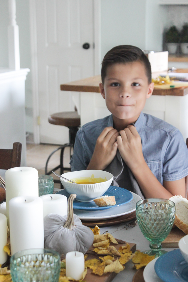 Boy tucking in napkin at a fall tablescape