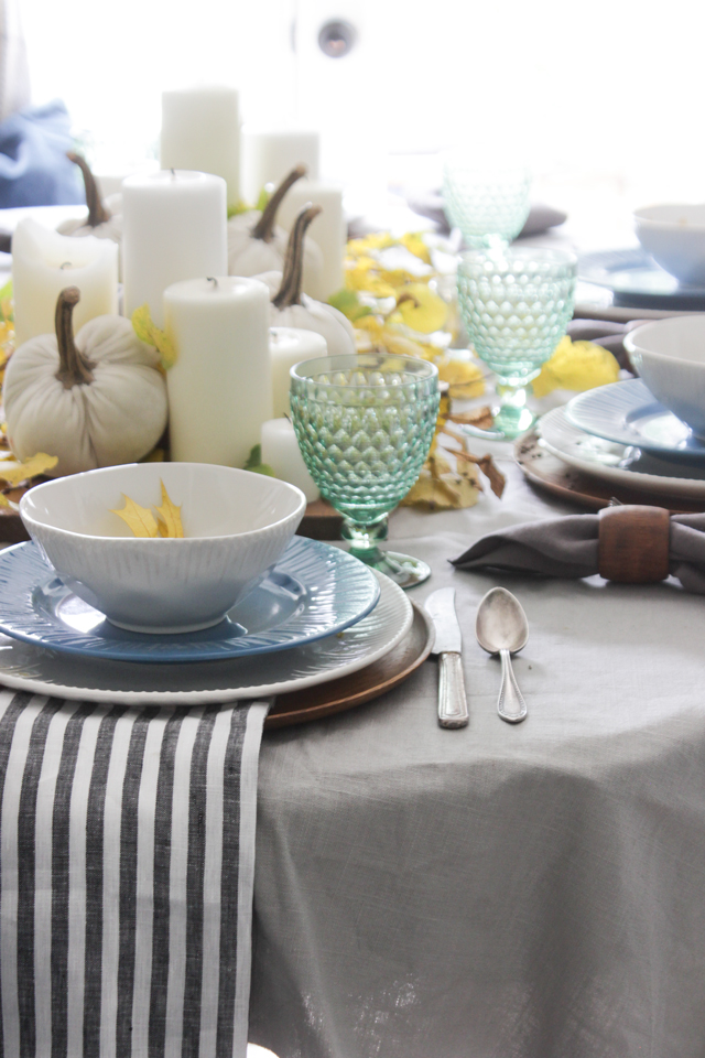 Fall tablescape with pillar candles, pumpkins, and striped napkin