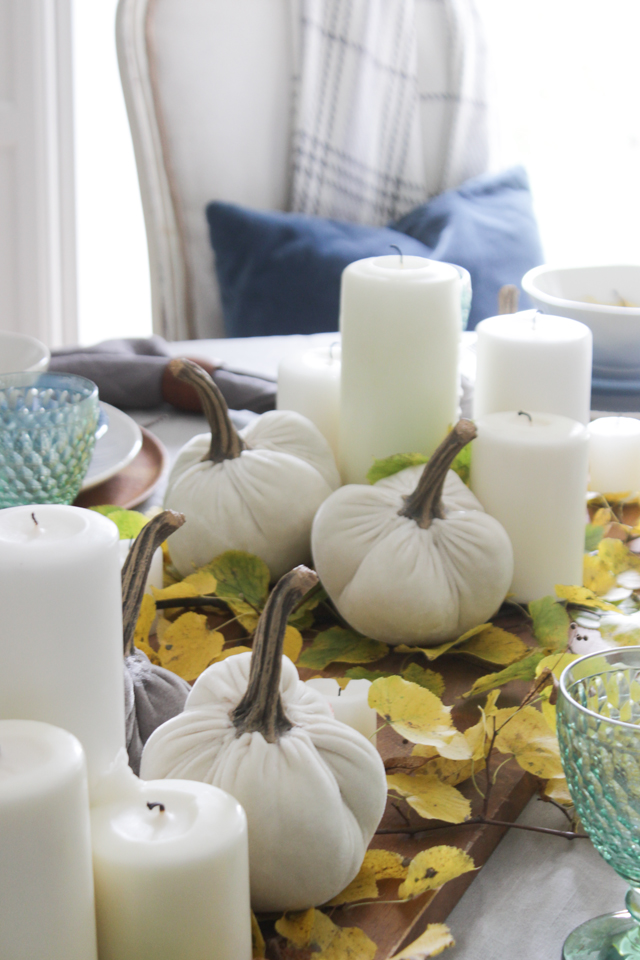 Fall table centerpiece with white pillar candles, velvet pumpkins, and fall foliage