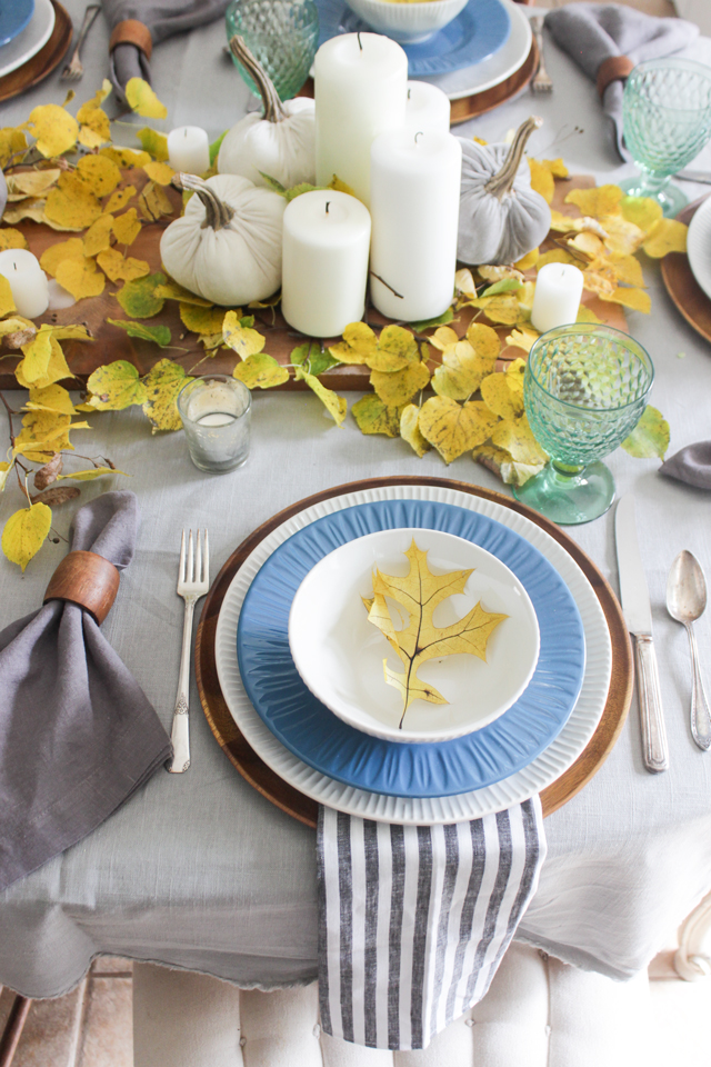 Fall table with yellow leaves, natural wood accents, blue and white plates, green goblets