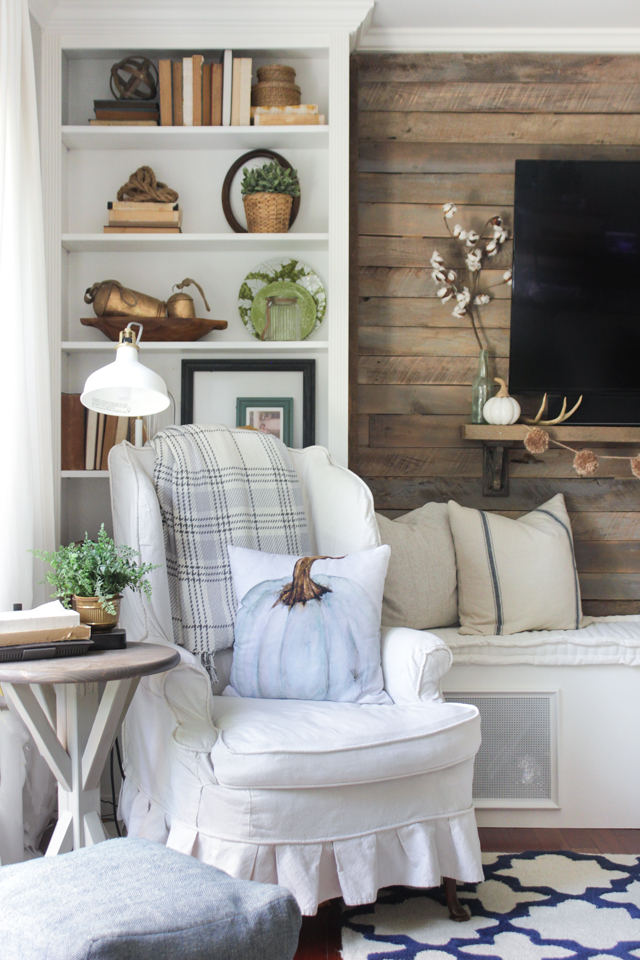 Slipcovered wing chair with pumpkin pillow- fall family room