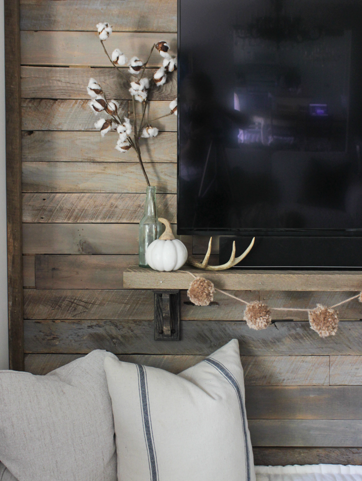 Pallet accent wall with cotton stems, pumpkin, antler, and pompoms on the shelf