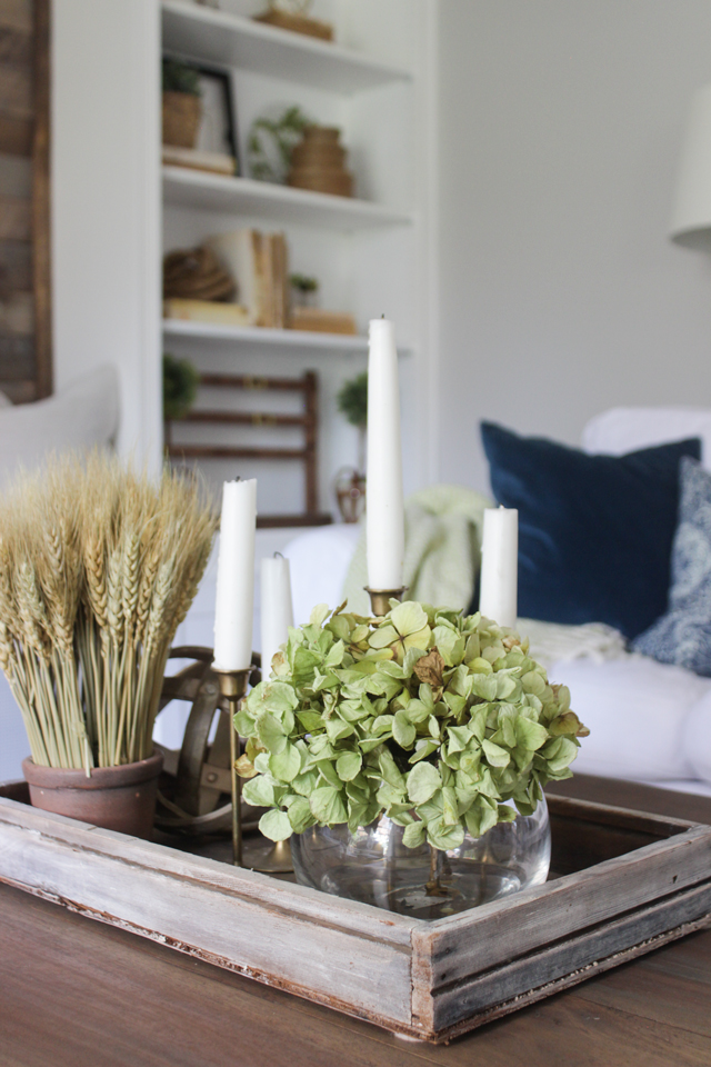 Dried green hydrangeas, wheat, and taper candles for coffee table centerpiece
