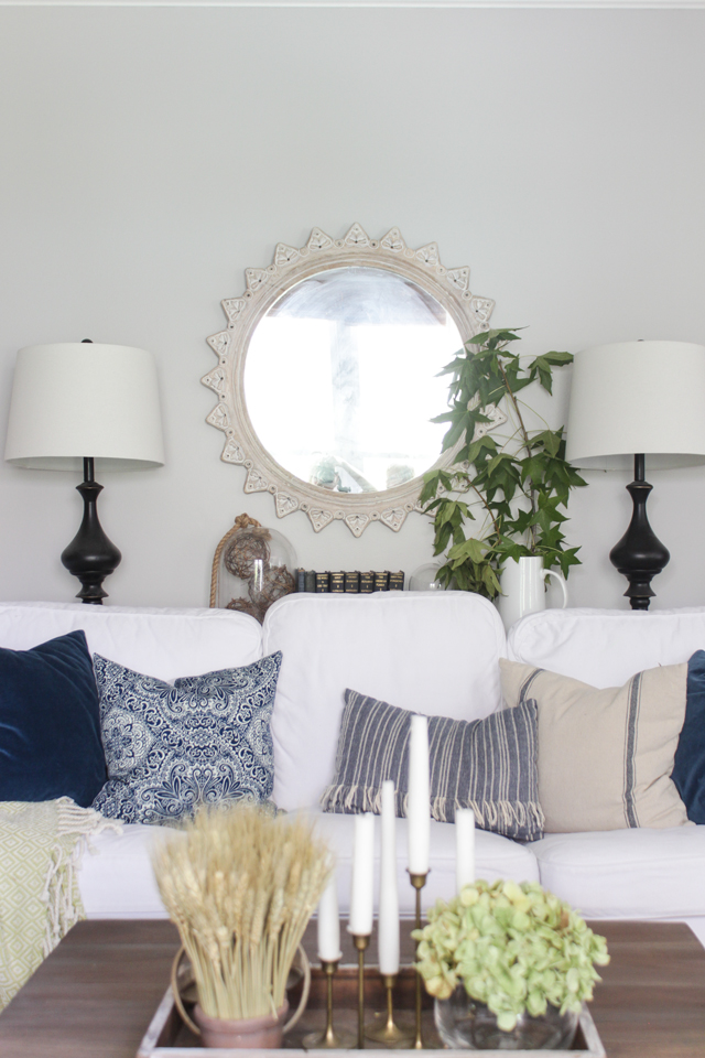 Round mirror over white couch, navy patterned pillows, and green fall foliage