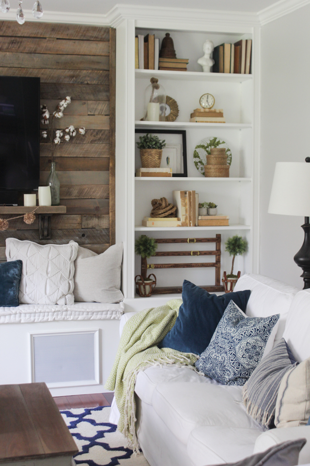 Built in bookcase with neutral decor, navy and green accents
