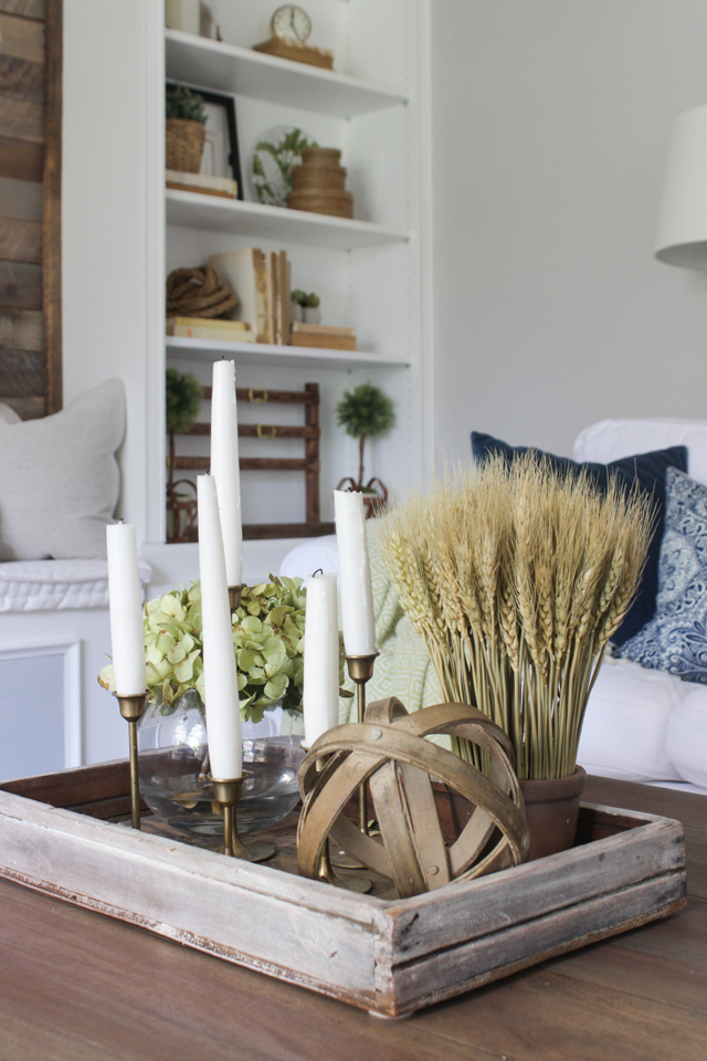 Coffee table styling with brass candlesticks, wheat grass, and wooden orb