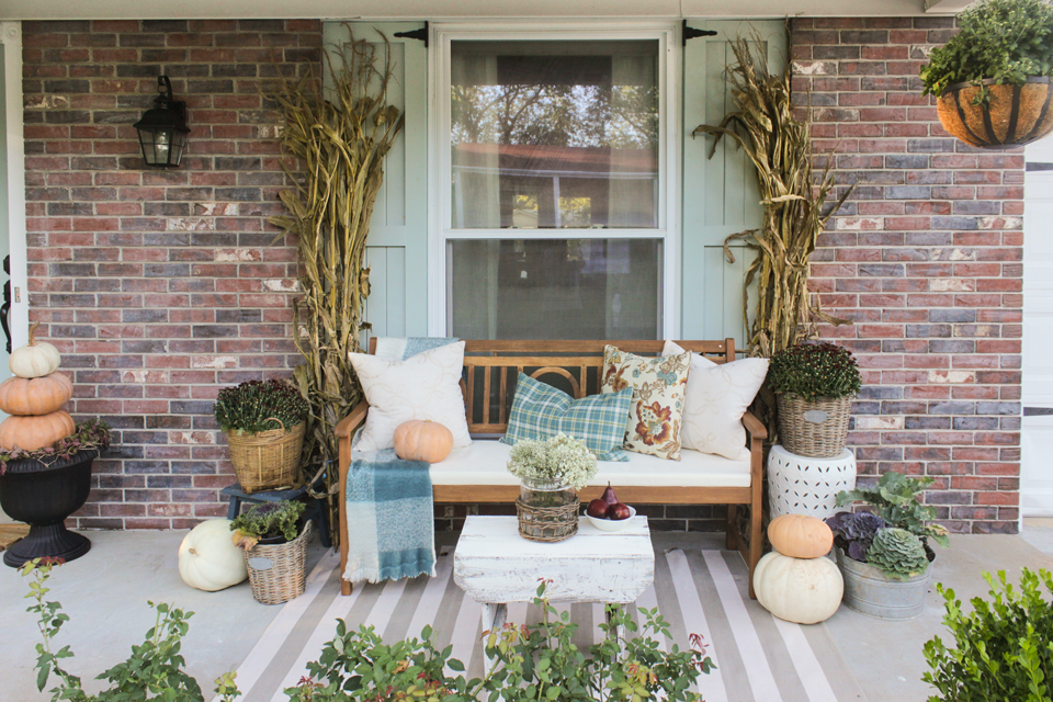Fall front porch with wooden bench, pillows, cornstalks, and pumpkin topiaries