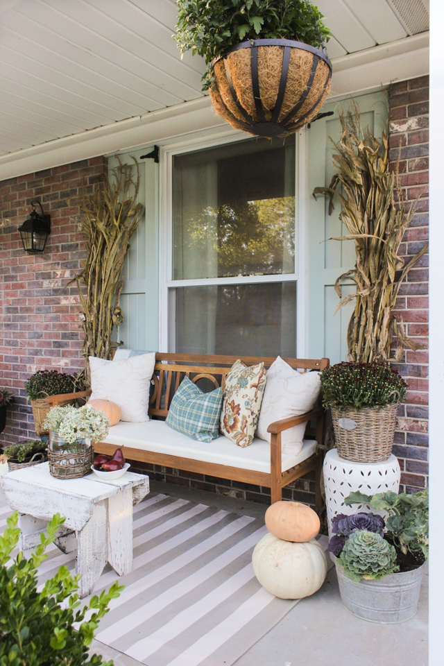 Fall front porch with wooden bench, pillows, cornstalks, and mums