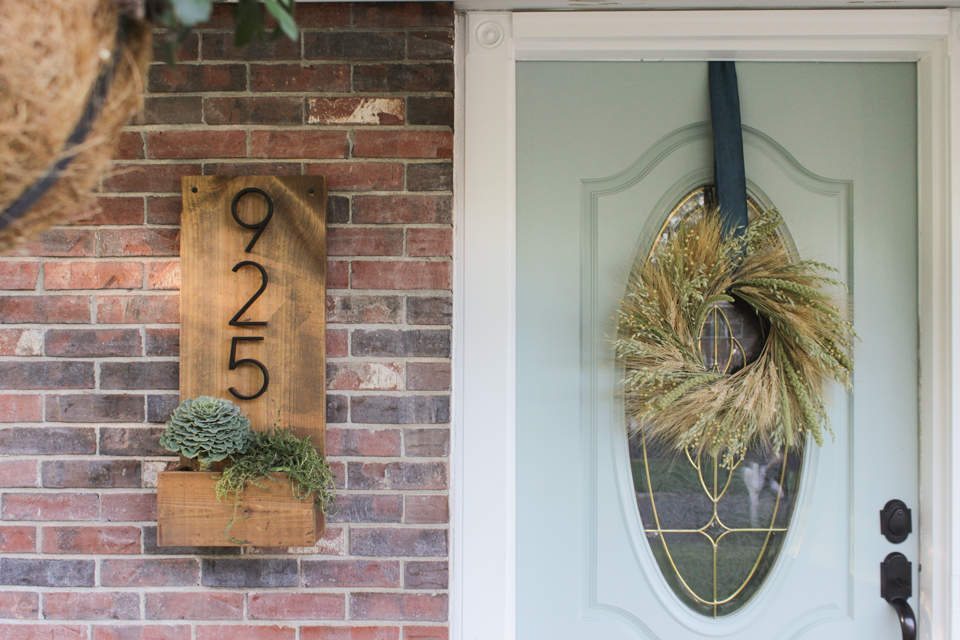 Wheat wreath on an aqua front door, and a wooden number sign with planter