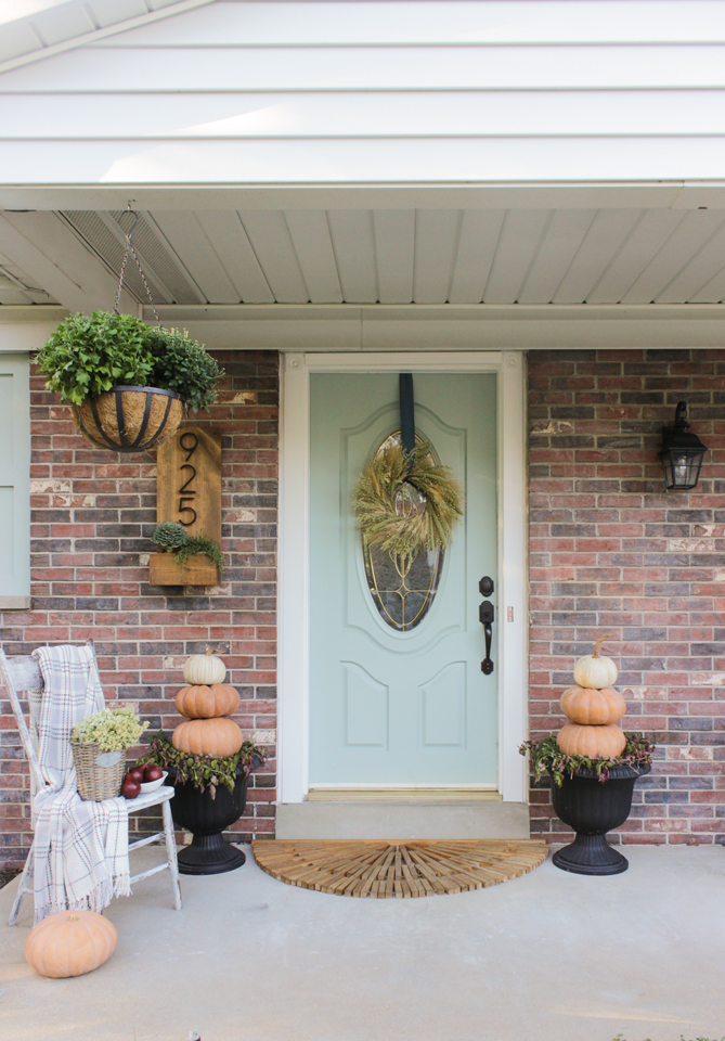 Fall front porch with pumpkin topiaries, wheat wreath, and wooden chair with throw