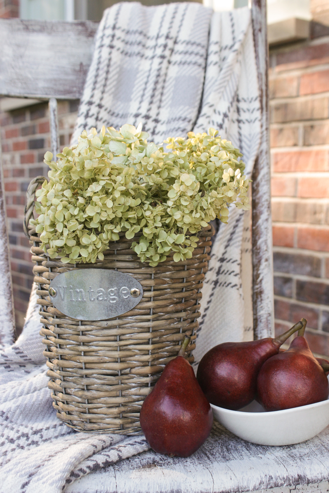 Vintage wicker basket, dried hydrangeas, red pears, and gray flannel throw