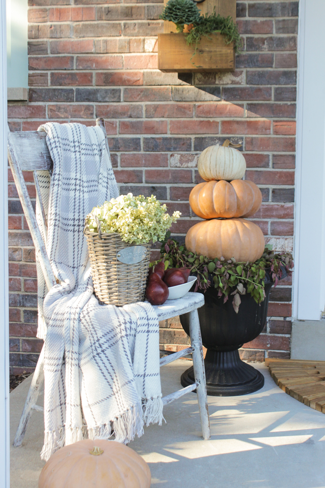 Farmhouse chair, flannel throw, and pumpkin topiary for fall