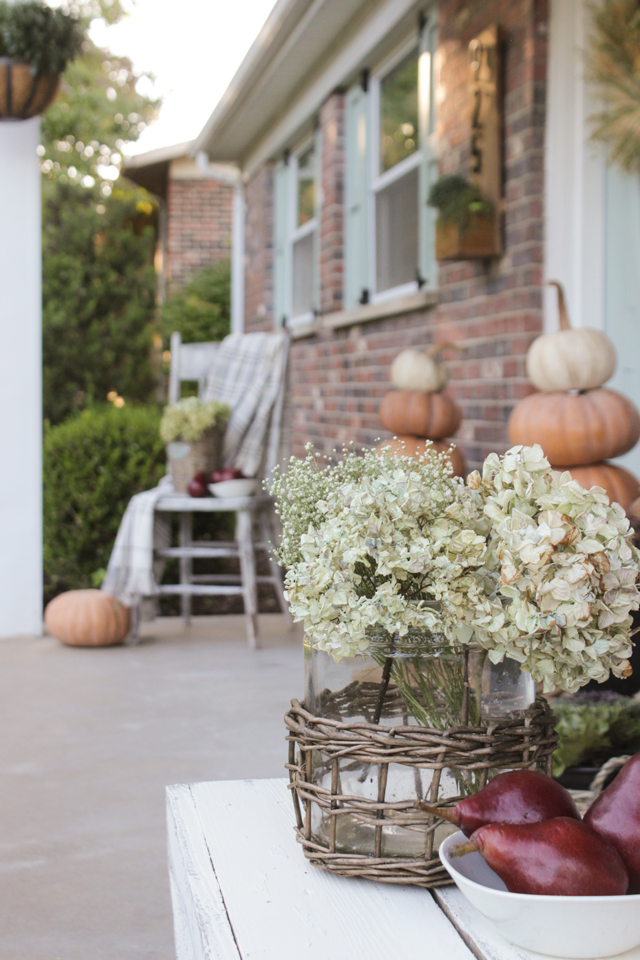 Fall front porch with wooden bench, pillows, cornstalks, and pumpkin topiary